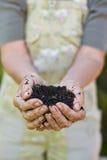 Oude vrouw met een handvol van compost royalty-vrije stock foto