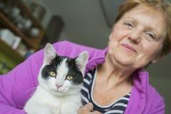 Oude vrouw met een kat - dierlijke therapie stock afbeeldingen