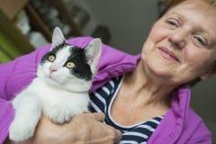 Oude vrouw met een kat - dierlijke therapie stock fotografie