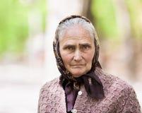 Oude vrouw met hoofddoek openlucht Royalty-vrije Stock Foto