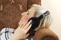 Oude vrouw met hoofdtelefoons in bank Royalty-vrije Stock Afbeeldingen