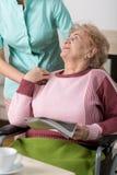 Oude vrouw met tijdschrift stock foto's