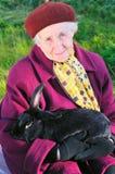 Oude vrouw met zwart konijn Stock Afbeeldingen