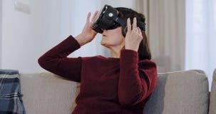 Oude vrouw op de bank die voor het eerst een virtuele werkelijkheidsglazen gebruiken aan het onderzoeken van de wereld, is zij ge stock video