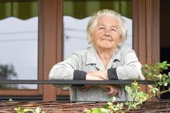 Oude vrouw op de portiek Royalty-vrije Stock Fotografie