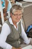 Oude vrouw in openluchtrestaurant Stock Fotografie