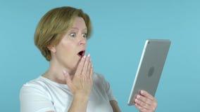 Oude Vrouw in Schok terwijl het Gebruiken van Tablet die op Blauwe Achtergrond wordt geïsoleerd stock videobeelden