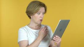 Oude Vrouw in Schok terwijl het Gebruiken van Tablet die op Gele Achtergrond wordt geïsoleerd stock footage