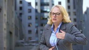 Oude vrouwelijke manager die plotselinge borstpijn voelen die op telefoon, nervositeit spreken stock videobeelden