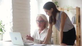 Oude vrouwelijke mentor die online app toont aan nieuw werknemersmeisje stock videobeelden