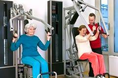 Oude Vrouwen die bij Gymnastiek met Instructeur uitoefenen stock afbeeldingen