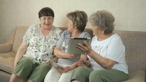 Oude vrouwen die de digitale tabletten houden stock video