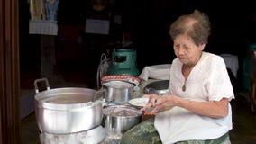 Oude vrouwen die Thaise zoete traditionele slang koken stock videobeelden