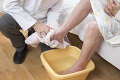 Oude vrouwen doorwekende voeten in een kom water stock afbeelding