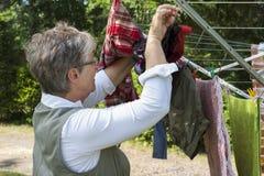 Oude vrouwen hangende wasserij Stock Foto's