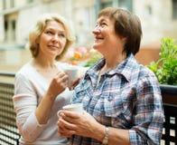 Oude vrouwen op balkon met koffie Royalty-vrije Stock Afbeeldingen