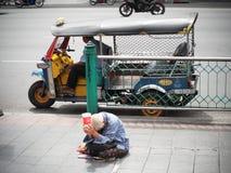 Oude vrouwenbedelaar die voor schenkingen op de stoep in de stad bedelen Royalty-vrije Stock Afbeelding