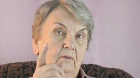 Oude vrouwengolven haar wijsvinger voor gezicht stock video