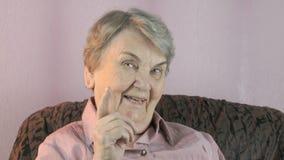 Oude vrouwengolven haar wijsvinger voor gezicht stock footage