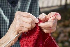 Oude vrouwenhanden die een rode sweater breien Stock Afbeeldingen