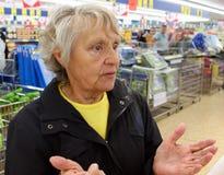 Oude vrouwentribunes hulpeloos in een supermarkt stock afbeeldingen