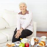 Oude vrouwenzitting bij ontbijt stock foto