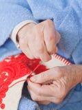 Oude vrouwenzitting op het bed, en het naaien van iets Royalty-vrije Stock Afbeelding