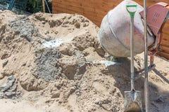 Oude vuile concreet-mixer dichtbij zandhoop bij kleine bouwwerf Kleine draagbare cement het mengen zich machine thuis stock afbeeldingen