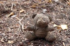 Oude vuile die teddybeer op de grondgrond wordt veronachtzaamd royalty-vrije stock afbeelding