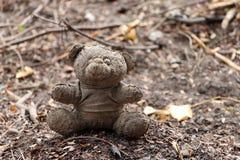 Oude vuile die teddybeer op de grondgrond wordt veronachtzaamd stock fotografie