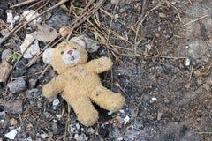 Oude vuile die teddybeer op de grondgrond wordt veronachtzaamd Beëindigen van kinderjaren stock fotografie