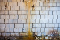 Oude vuile muur met witte vierkante tegels Stock Afbeeldingen