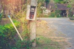 Oude wattuurmeter van elektriciteit voor gebruik in huistoestel op elctric pool bij dorp royalty-vrije stock fotografie