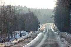 Oude weg tussen het hout een reis uit stad op een mistige dag heuvelig gebied, op de horizon een groot aantal bomen, bergen E stock afbeelding