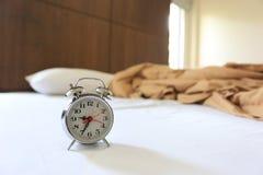 Oude wekker op bed in slaapkamer stock afbeelding
