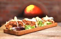 Oude wereld Italiaanse bruschetta die met vleessaus en kaas wordt bedekt royalty-vrije stock foto
