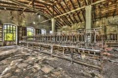 Oude wevende weefgetouwen en spinnende machines bij een verlaten fabriek stock foto