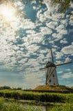 Oude windmolen naast kanaal en zonlicht in Damme stock foto's