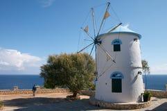 Oude windmolen op het eiland van Griekenland op het overzeese strand royalty-vrije stock fotografie