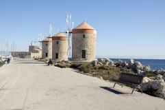 Oude windmolens op de steenachtige kustlijn van Rhodos in haven, oude historische gebouwen, bezienswaardigheid, blauwe hemel stock afbeeldingen