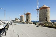 Oude windmolens op de steenachtige kustlijn van Rhodos in haven, oude historische gebouwen, bezienswaardigheid, blauwe hemel royalty-vrije stock afbeeldingen
