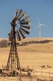 Oude windpomp en nieuwe die windgenerators door de hete lucht wordt vervormd. Zuid-Australië. Royalty-vrije Stock Foto