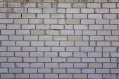 Oude witte gele bakstenen muur met barsten en krassen Ruwe Oppervlaktetextuur royalty-vrije stock afbeelding