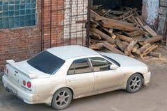 Oude witte sportwagen Nissan dichtbij de garages stock fotografie