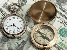 Oude zak watxh en oud kompas op dollars Stock Foto's