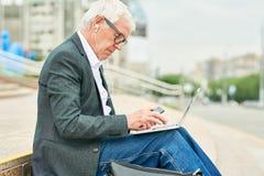 Oude zakenman gebruikend laptop en luisterend aan muziek stock afbeeldingen