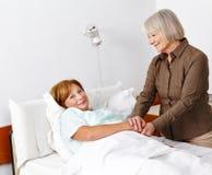 Oude zieke vrouw die bezoeker krijgen royalty-vrije stock afbeelding