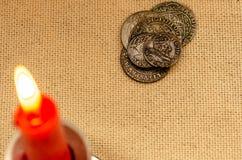 Oude zilveren muntstukken en brandende kaars stock foto's