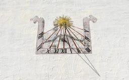 Oude zonnewijzer op witte muur in Wolfenschiessen in Zwitserland Stock Fotografie