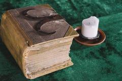 Oude zware boek en kaars op de middeleeuwse lijst stock afbeeldingen